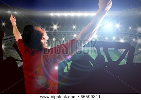 Cheering football fan in red jersey against large football stadium with lights poster