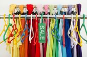 Sale sign for summer clothes on a clearance rack with colorful summer outfits and accessories. poster