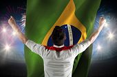 Excited football fan cheering against fireworks exploding over football stadium and brasil flag poster