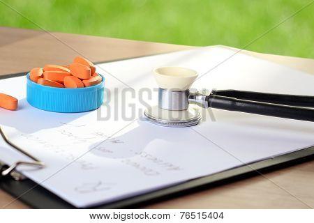 Orange Pills,  Prescription And Phonendoscop On A Green  Background
