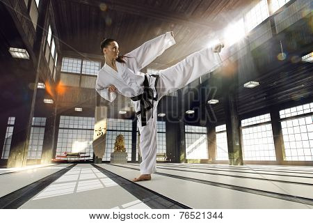 Karate woman in action on old sports hall