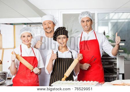 Portrait of confident chef team gesturing thumbsup together in commercial kitchen
