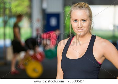Portrait of beautiful female athlete standing in Cross-Fitess Center