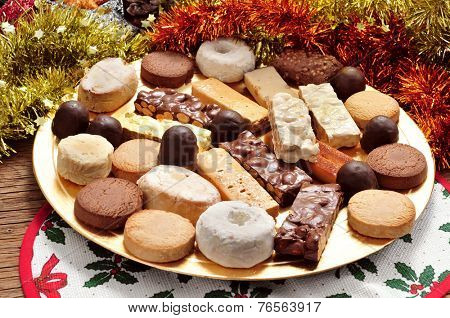 a tray with different turron, polvorones and mantecados, typical christmas confections in Spain, on an ornamented table poster