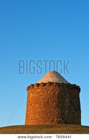 Stone Monument On A Hilltop At Sunset