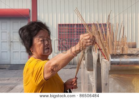 Old Chinese woman burns incense in the temple