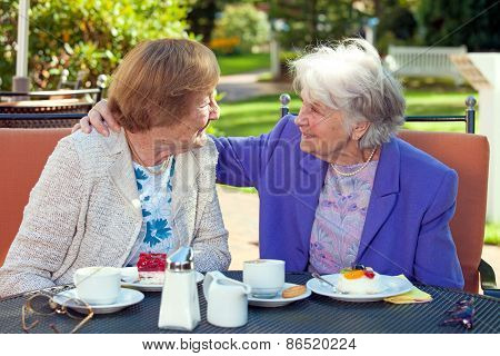 Cheerful Old Women Talking At The Outdoor Table