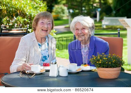 Senior Female Best Friends Relaxing At The Table