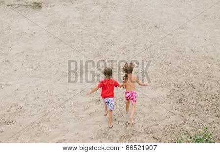 Fraternal twins running barefoot at the beach