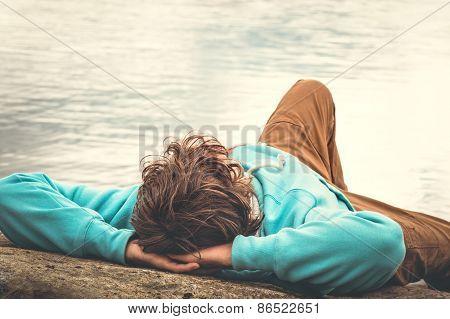 Young Man laying relaxing outdoor with lake on background