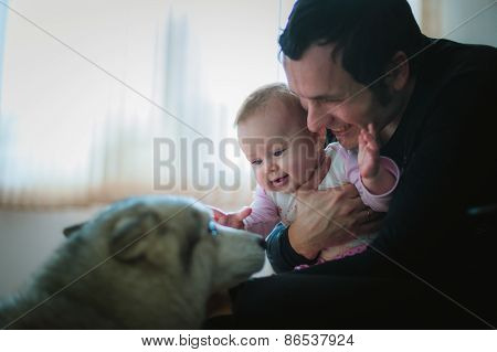 Image of young dad with cute little daughter in his arms