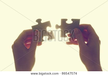 Joining two pieces of jigsaw puzzle. Backlit, isolated on white. Search for the solution, solving the problem, answer, business connection concept. Vintage