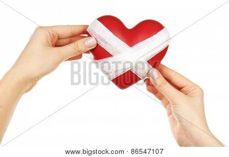 Female hands holding bandaged heart isolated on white