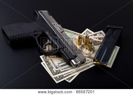 gun with bullet on US dollar banknotes crime or corruption concept on black backgroud poster