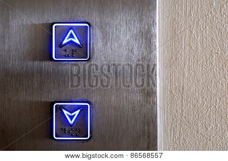 Elevator buttons glowing in neon blue up and down poster
