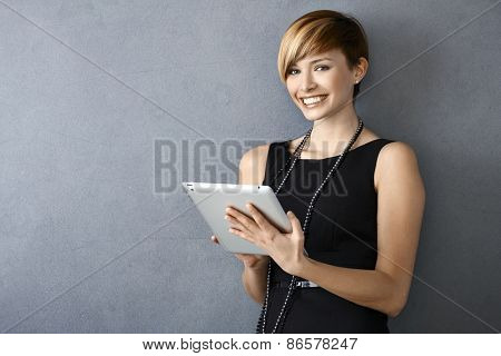Portrait of elegant young woman in black dress using tablet leaning to wall