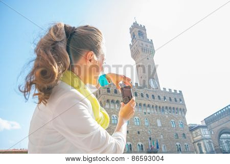 Young woman taking photo of palazzo vecchio in florence italy. rear view poster