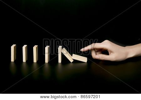 Female Hand Pushing A Row Of Wooden Domino