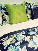 Close-up of a bed. Blue and green bed linen with floral design. poster