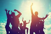 Happy friends, family jumping together in a circle having fun and expressing emotions of joy, freedom, success. Silhouettes on sunny sky poster