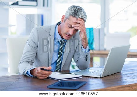 Irritated businessman trying to work in office
