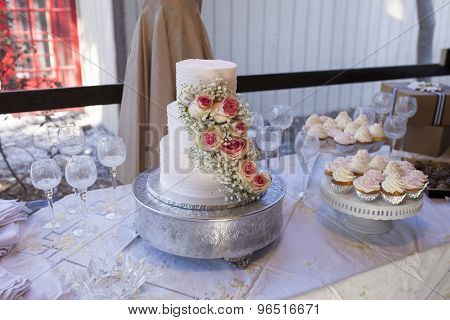 Three tiered wedding cake with roses on table with vintage theme