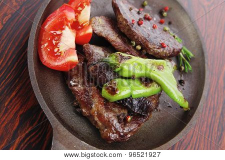 fresh roast beef fillet mignon on old retro style cast iron pan on retro wooden table as background with rosemary peppercorn and tomatoes poster