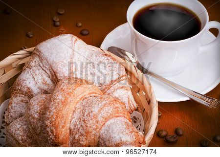 Two Fresh-baked Croissants And Cup Of Black Coffee With Beans On Wooden Table. Continental Breakfast