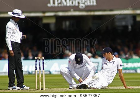 LONDON, ENGLAND. AUGUST 16 2012 England's Graeme Swann checks the studs of England's Steven Finn during the third Investec cricket  test match between England and South Africa, at Lords Cricket Ground