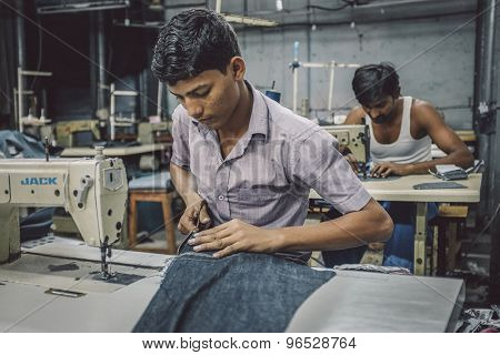 MUMBAI, INDIA - 12 JANUARY 2015: Indian workers sew in clothing factory in Dharavi slum. Post-processed with grain, texture and colour effect.
