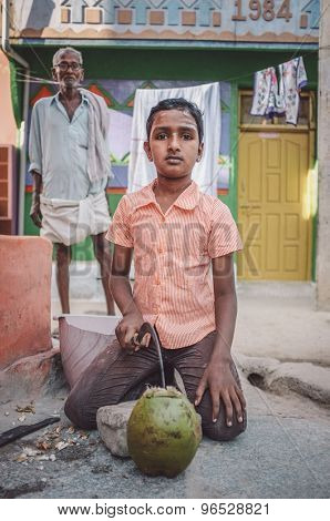 KAMALAPURAM, INDIA - 02 FABRUARY 2015: Indian boy opening a coconut in-front of house in a town close to Hampi. Post-processed with grain, texture and colour effect.
