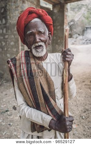 GODWAR REGION, INDIA - 13 FEBRUARY 2015: Blind Rabari tribesman holds stick in courtyard. Post-processed with grain, texture and colour effect.