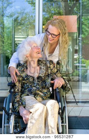 Medical Assistant And An Elderly Laughing Together