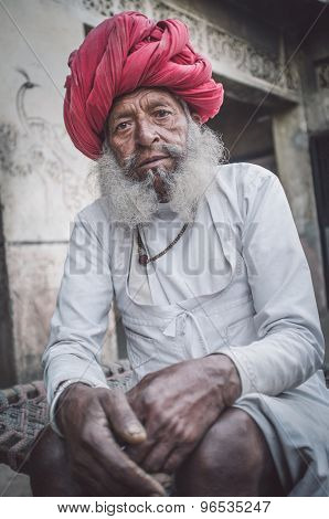GODWAR REGION, INDIA - 12 FEBRUARY 2015: Elderly Rabari tribesman with traditional turban, clothes and long beard. Post-processed with grain, texture and colour effect.
