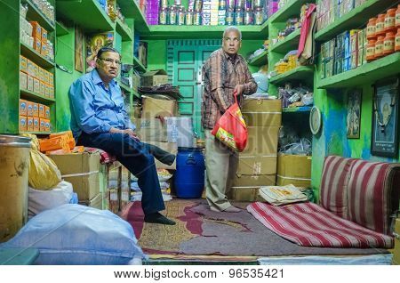 JODHPUR, INDIA - 07 FEBRUARY 2015: Shop owner waiting while customer looks for goods to buy. Apart from cheap labourers, shop owners also stay in stores until late working hours.