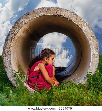 Homeless teenager girl sits on his haunches in the concrete pipe