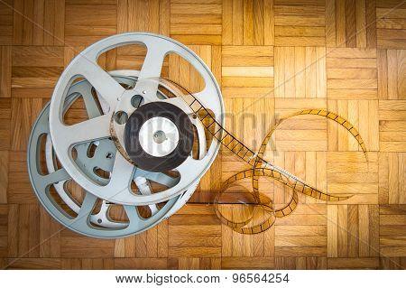 35 Mm Movie Film Reel On Wooden Floor