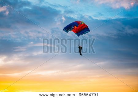Skydiver On Colorful Parachute In Sunny Sky
