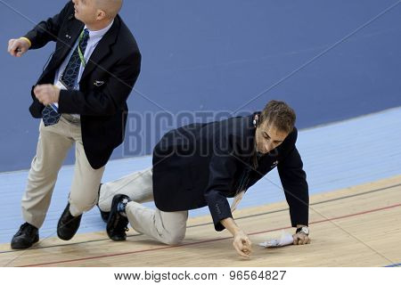 LONDON, ENGLAND. FEBRUARY 18 2012: Officials check the track after a crash at the UCI Track Cycling World Cup at the London Velodrome, Queen Elizabeth 2nd Park