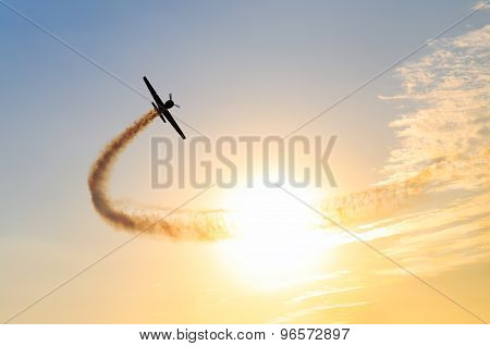 Silhouette of an airplane performing flight at airshow at sundown
