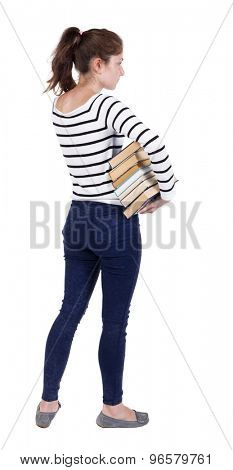 A girl carries a heavy pile of books. back view. Rear view people collection.  backside view of person.  Frenchwoman in vest is holding a stack of books under his arm and looks thoughtfully ahead.