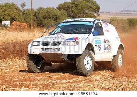 Drifting White Bmw Rally Car Kicking Up Dust On Turn.