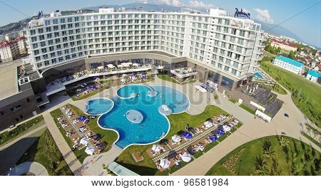 RUSSIA, SOCHI - JUL 25, 2014: Tourists get rest around and in pool of hotel Radisson Blu at summer sunny day. Aerial view. Photo with noise from action camera.