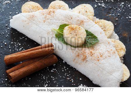Casabe (bammy beiju bob biju) - flatbread made from cassava (tapioca) with banana and cinnamon on pan. Selective focus poster