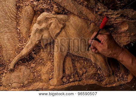 The close up carver or engraver are doing handicraft wooden elephant.