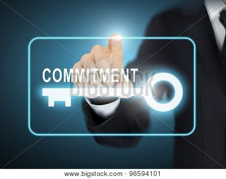 male hand pressing commitment key button over blue abstract background poster
