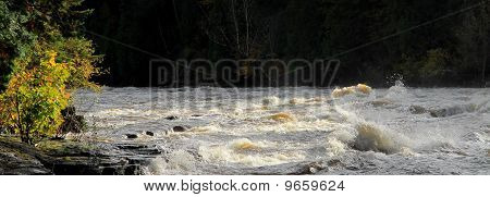 Tumultuous River With Fall Landscape.