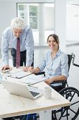 Confident business woman in wheelchair working at office desk with her male colleague and smiling at camera poster