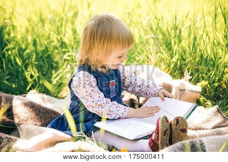 Little girl looks at pages of book while sitting on picnic blanket among long green grass in spring sunny day. Age of child 2 years and 4 month.