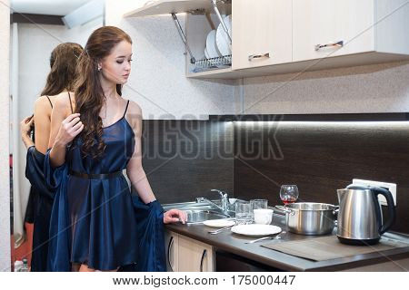 Brunette housewife in blue robe in the kitchen.
